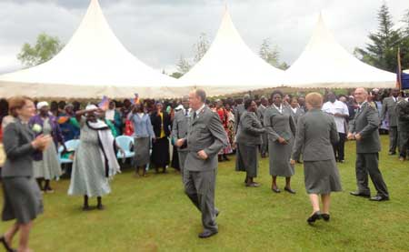 The General, Commissioner Silvia Cox and the territorial leaders join women from WORTH groups as they dance with excitement at Kamobo Corps