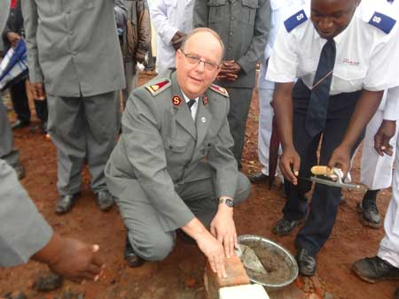 The General lays foundation stone of the Kakamega Central Corps in Kakamega Division, as the Corps Sergent Major looks on.