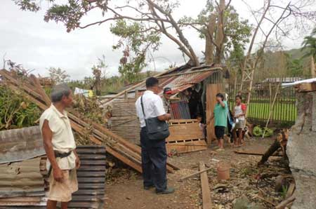 Salvation Army officer in Antique visiting a community in makeshift homes that were damaged by Typhoon Haiyan