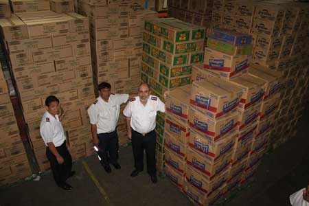 Colonel Wayne Maxwell, Lt. Colonel Alex Genabe Secretary for Program, and Major Reynaldo Magat at the SM warehouse in Manila with employees preparing 7 tons of food for dispatch to Tacloban
