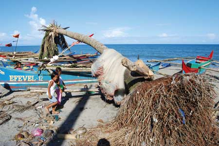 Children play on a beach near Tacloban, surrounded by beached fishing boats and uprooted trees photo by Major Dean Pallant