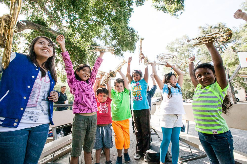 children smiling with hands in air outside