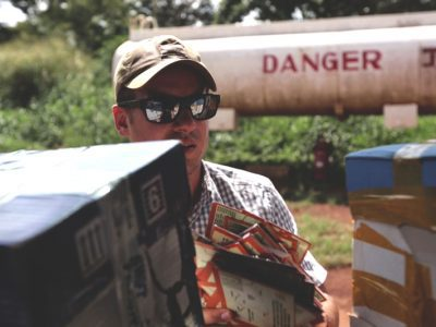 Sean Poole loads fliers, about LRA combatants who had successfully returned home, into a plane to drop over Uganda.