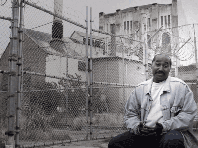 Man sitting outside on other side of fence