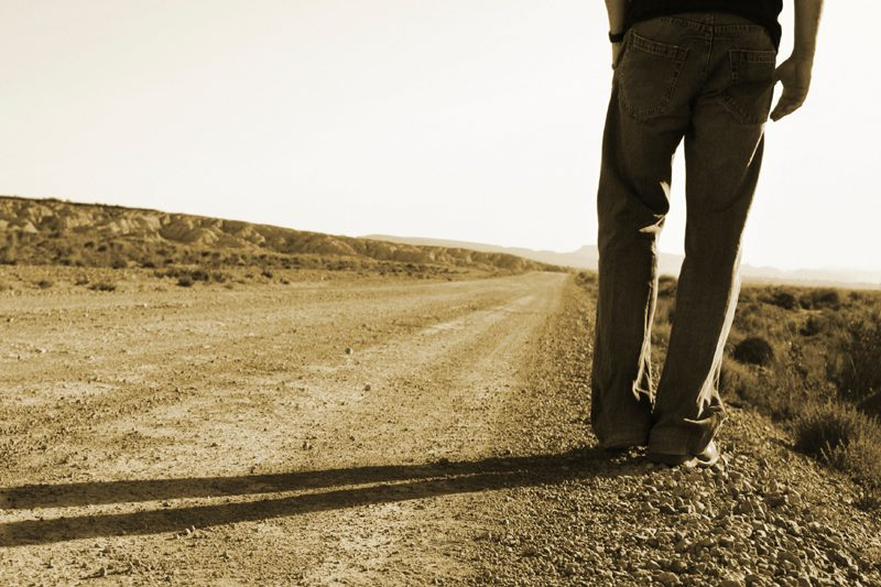 person standing on side of dirt road