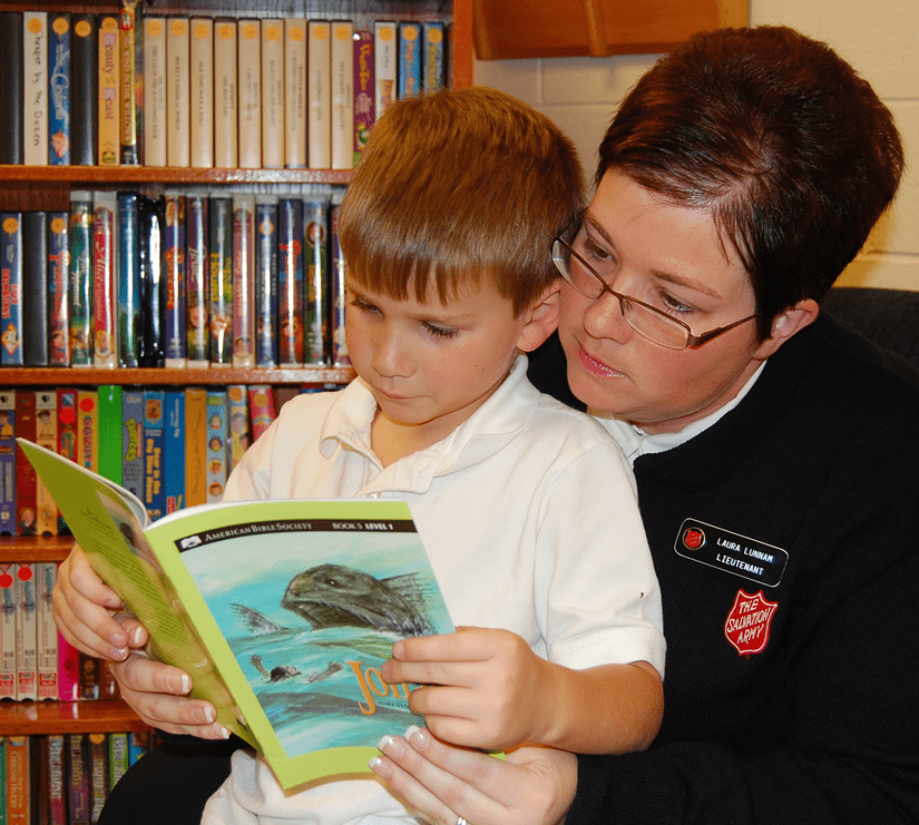 Salvationist reading with child on lap