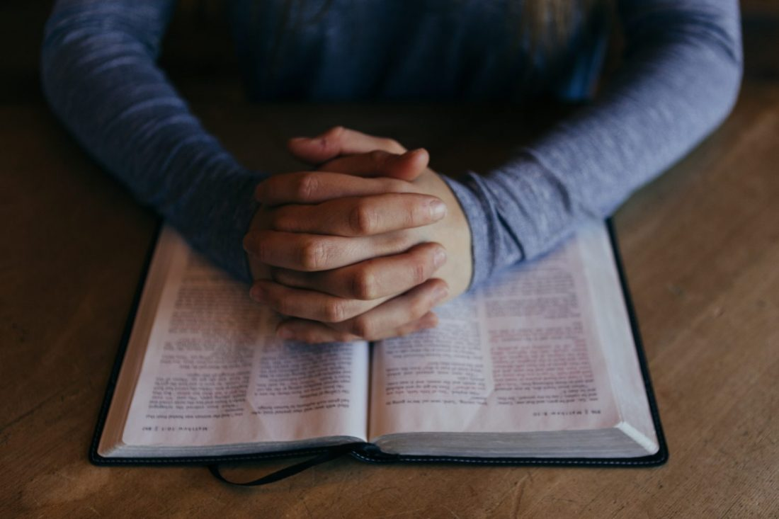 Hands folded over Bible