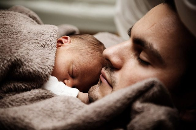 Man with baby sleeping on chest