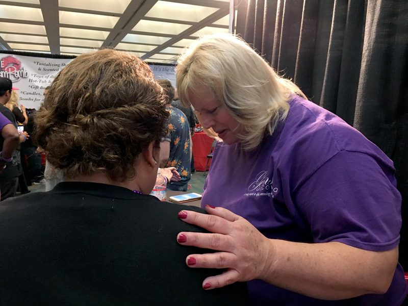 A volunteer prays with a visitor to The Salvation Army's AdultCon booth. | Photo by Jackeline Luna
