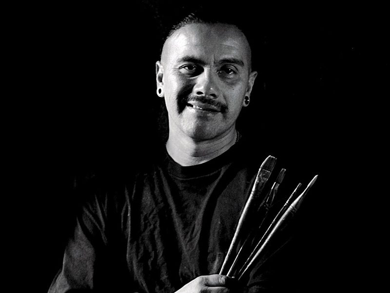 Man holding paint brushes in black and white