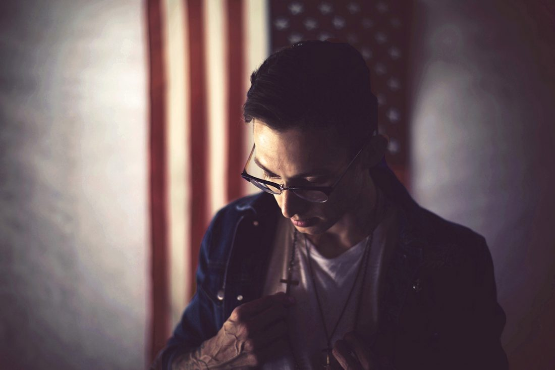 Man wearing cross necklace in front of American flag