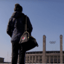 Person with gym bag standing outside Olympic building