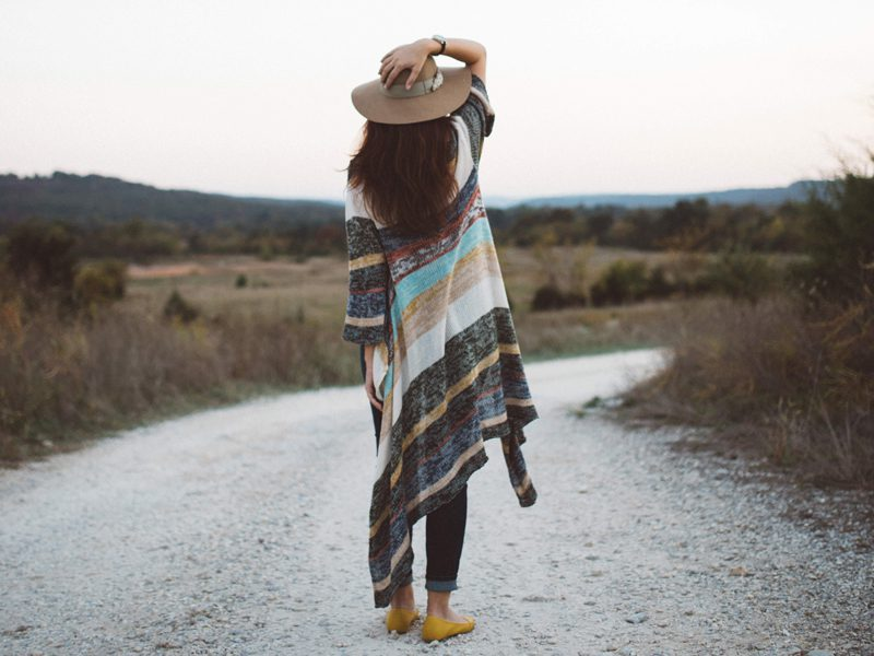 Woman holding hat outside on road