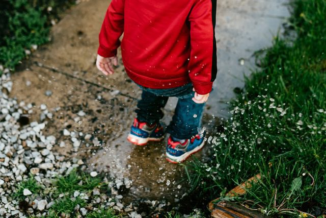 Child in red jacket jumping outside