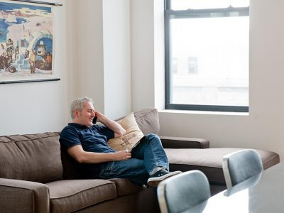 Man sitting on couch talking on phone