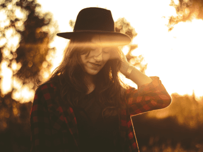 Woman with hat looking down and smiling