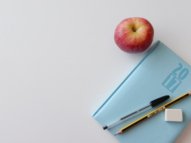 apple next to notebook and pen