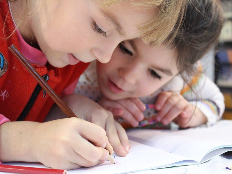 two young children writing