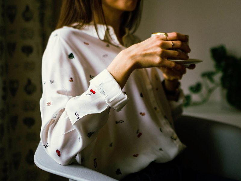 woman holding coffee cup with two hands