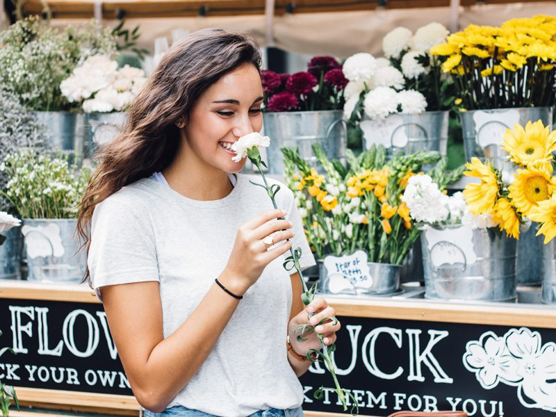Woman smiling while smelling flower
