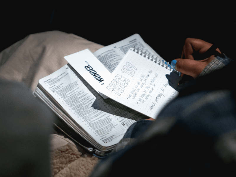 person with Bible and notes on lap