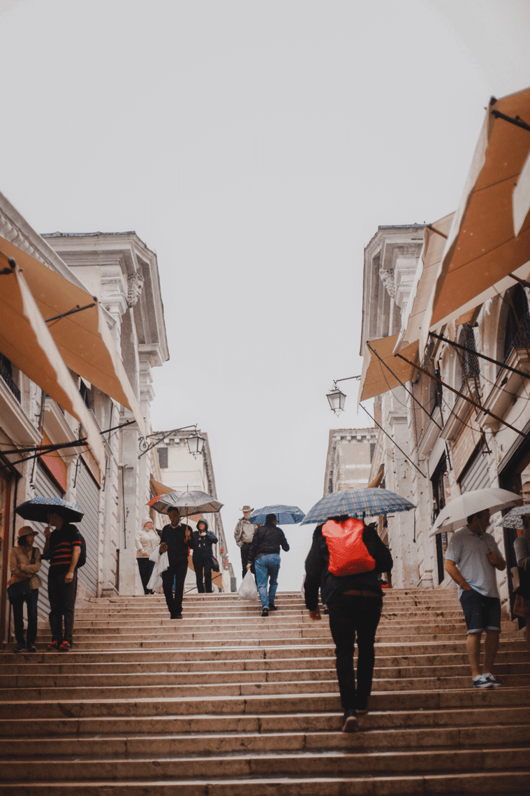 People on stairs with umbrellas