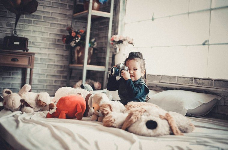 girl on bed with stuffed animals