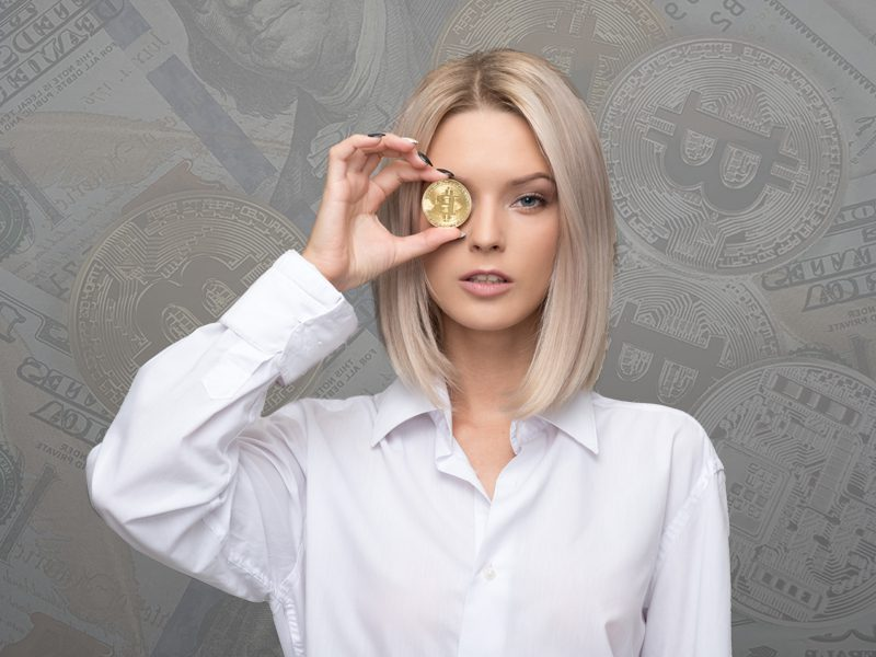 Woman holding gold coin with bitcoin logo