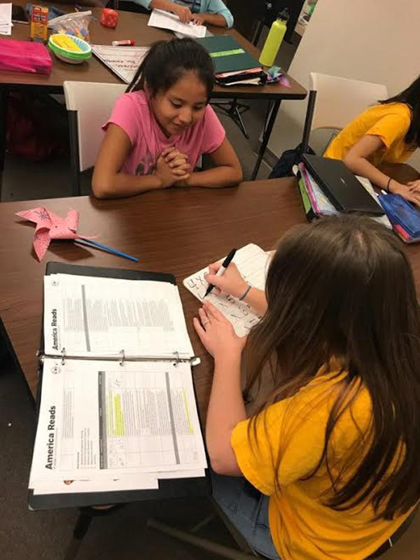 tutor helping young girl at table with homework