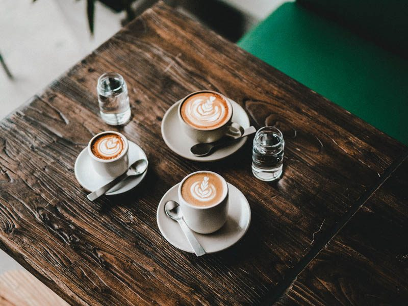 Three coffee cups on wooden table