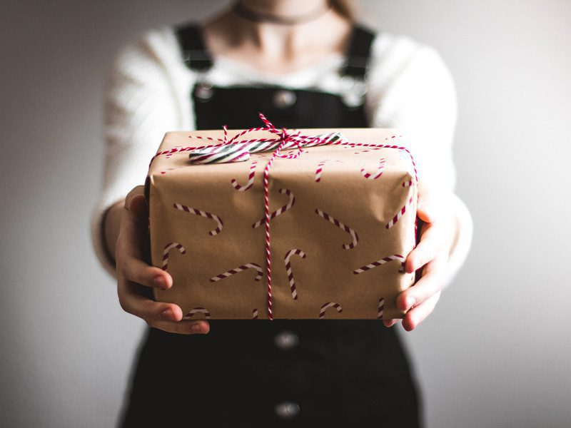 woman holding presents with candy cane wrapping paper