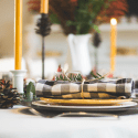 Single table setting on white table cloth in front of candles