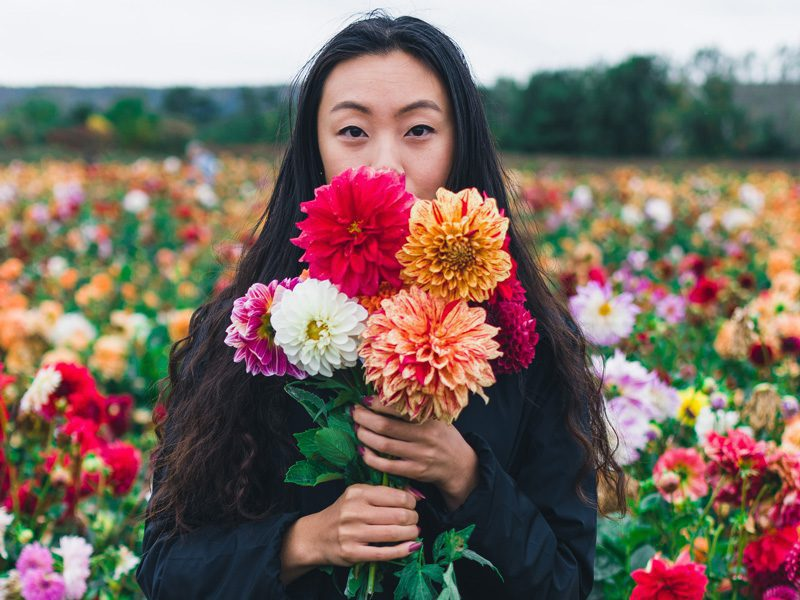 Young Woman holding flowers in front of her face