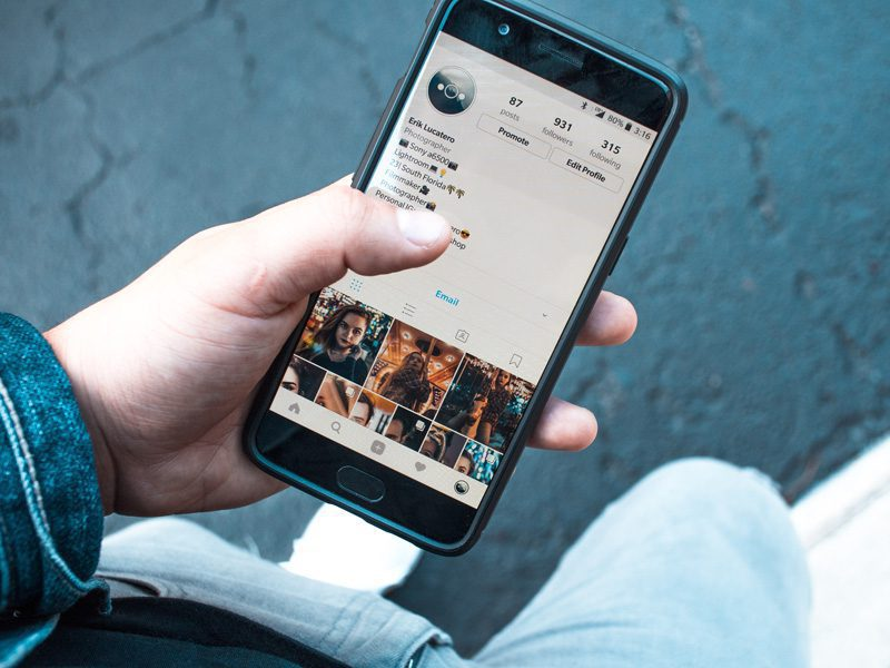 Hand holding phone with Instagram on screen