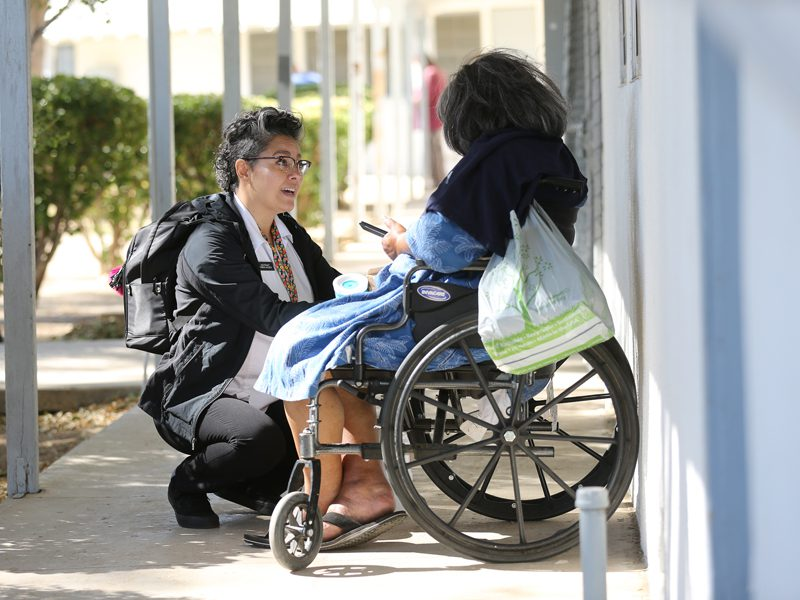 Female Officer talking with homeless woman in wheelchair