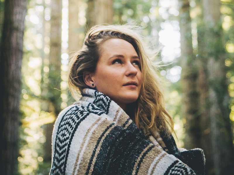Woman in blanket looking up at sky