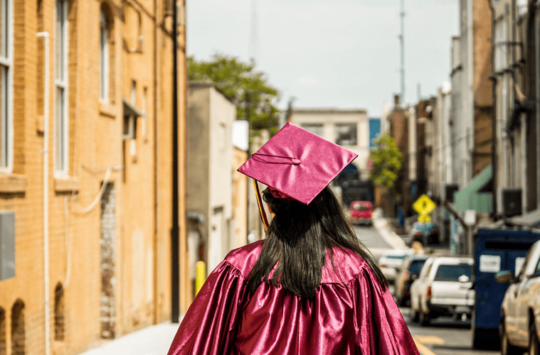 Female Graduate in Red Cap and Gown Walking Down Street