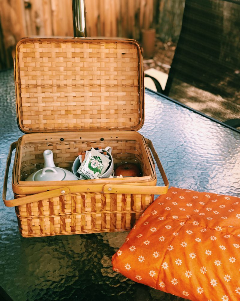Picnic Basket on Glass Table with Teapot and Tea Packets Inside