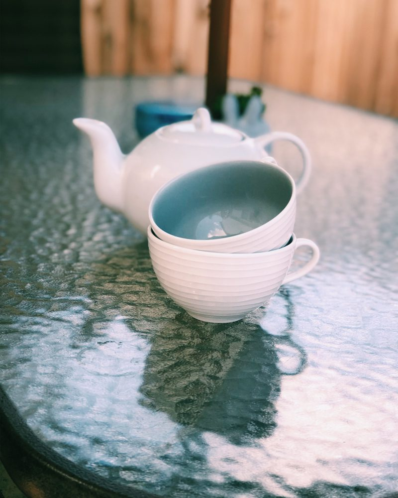 Tea Cups and Teapot on Glass Table
