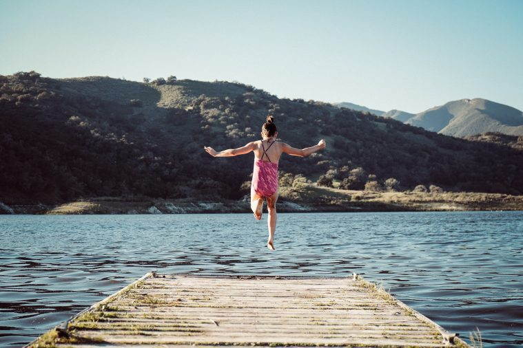 Young Girl Jumping Off Dock into Lake