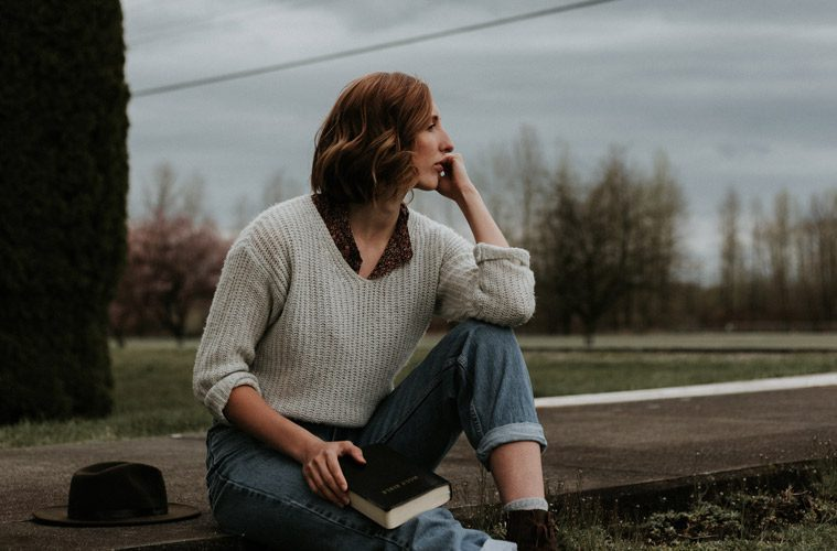 Woman Holding Bible Looking into Distance