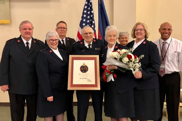 Majors Gerald and Suzanne Hill with group and award