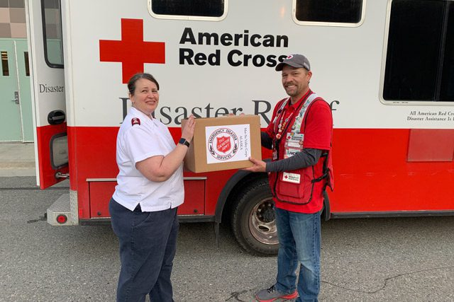 Red Cross and Salvation Army Workers in Front of Red Cross Truck with Box
