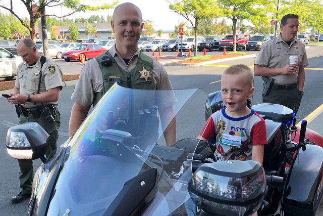 Child Sitting on Officer's Motorcycle with Smiling Cop
