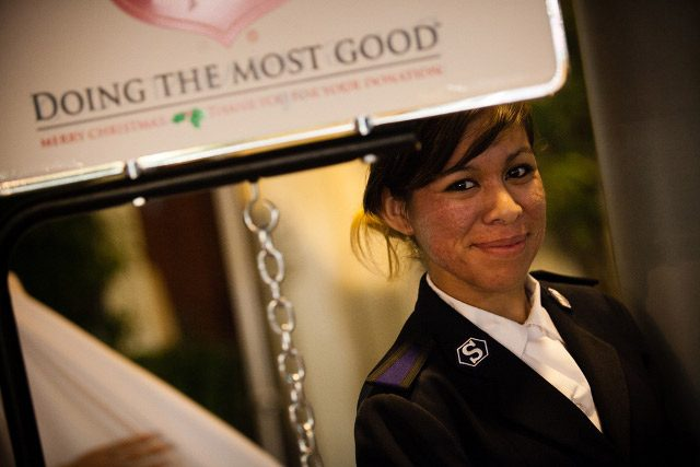 Cadet smiling next to Christmas Kettle