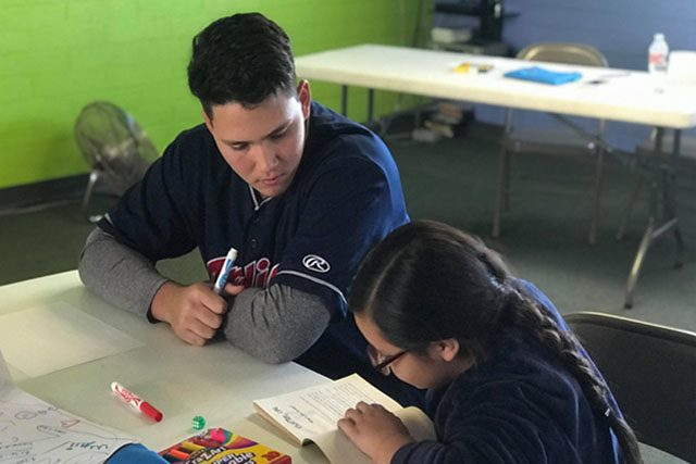 Cleveland Indians Recruit Helping Child with Homework