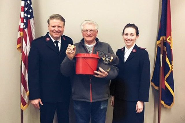 Man holding Krugerrand and kettle with Salvation Army soldiers