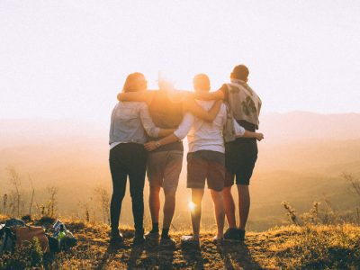 four people with arms around each other outside