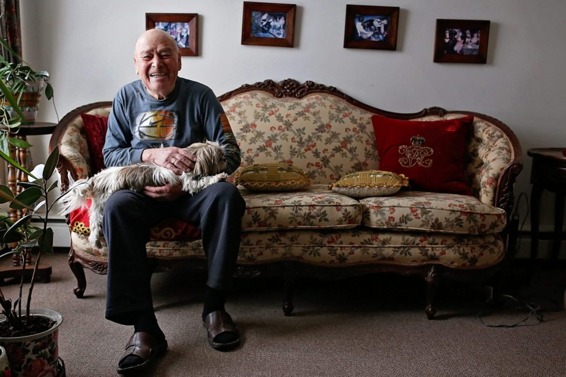 Elderly man sitting on couch with pet