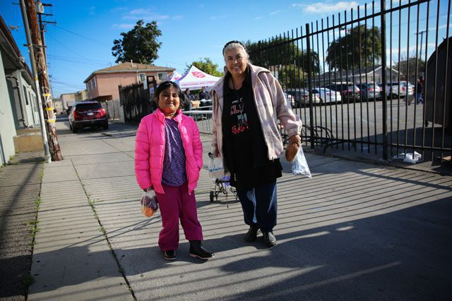 female child and older woman standing outside